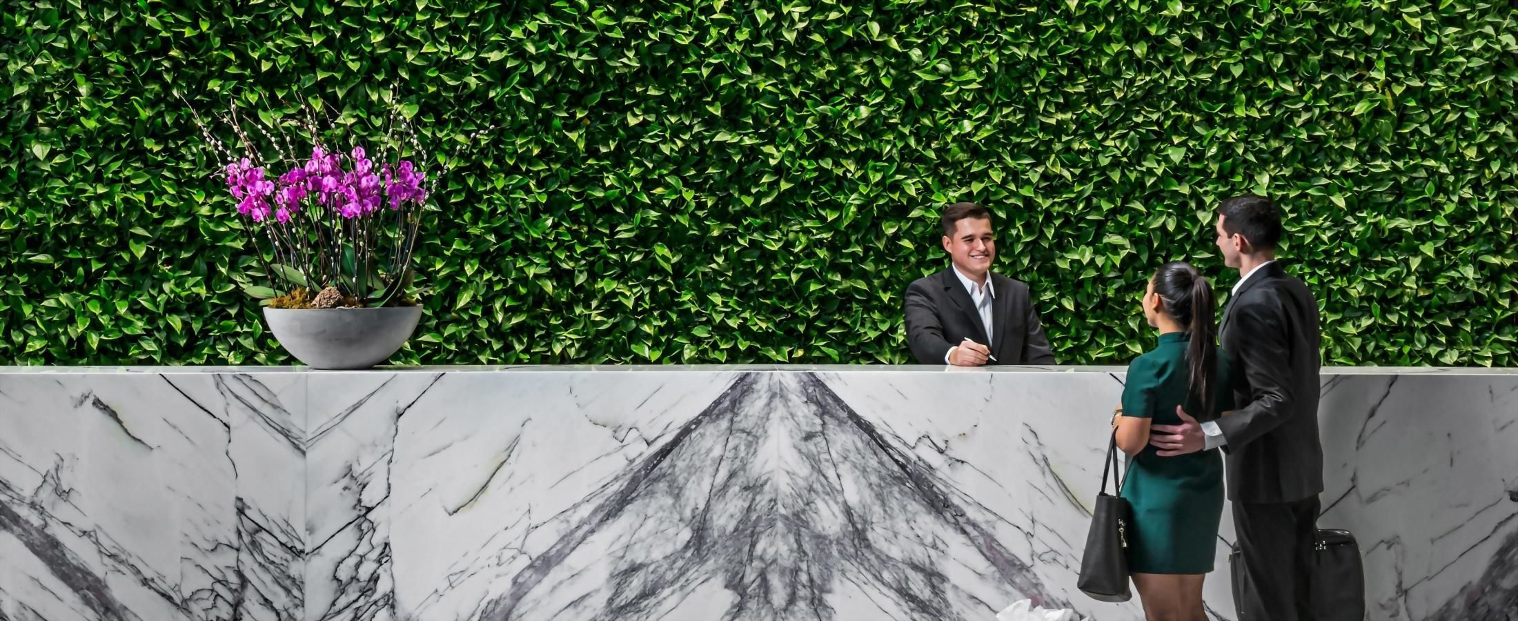 Two guests checking in at the large marble front desk with large green living wall behind it.
