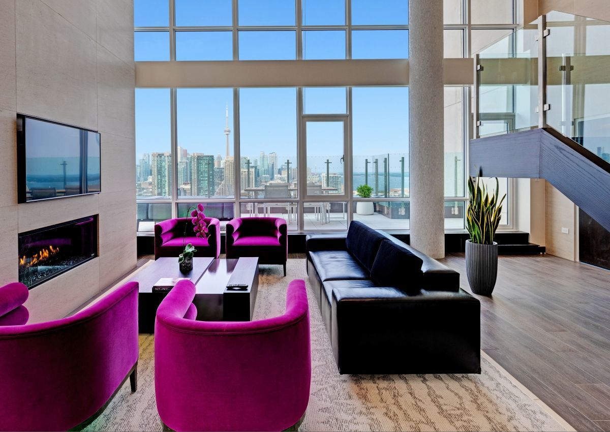 The Bi-level Penthouse suite with a view of the Toronto city skyline through the ceiling to floor windows. There are four purple plush chairs and a black leather couch in front of the fireplace with a coffee table between them. There is a vase with a plant beside the staircase leading up to the second level.